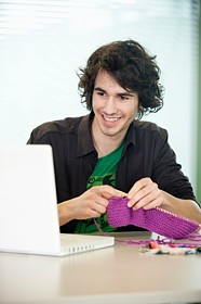 Happy guy knitting at computer