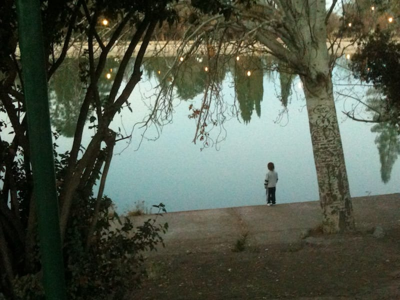 Kid standing by pond in the park in Mendoza