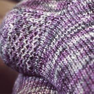 Closeup of eye-of-the-partridge heel stitch on a fingerin-weight toe-up sock
