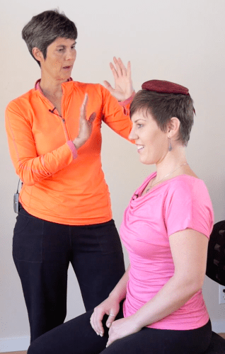 Liat Gat showing how to lengthen the neck using a head cushion placed on the head
