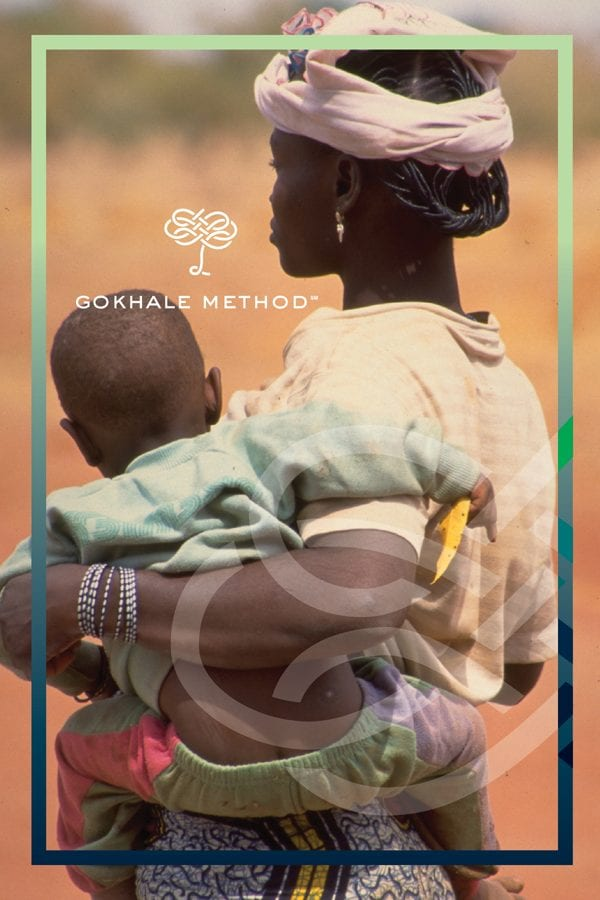 Woman from Burkina Faso carrying a child on her hip. She shows fantastic posture.